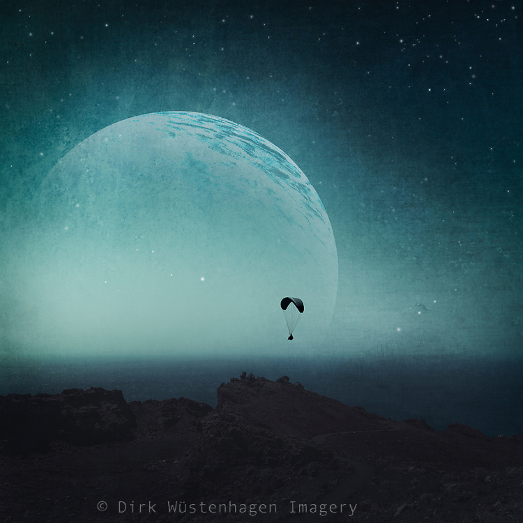 Landscape by the sea at night with the silhouette of a paraglider in front of an enourmous rising moon. Manipulated photograph