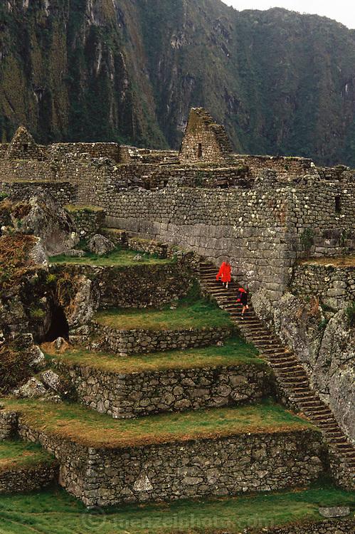 Hikers in rain at the Inca ruins at Machu Picchu, Peru.