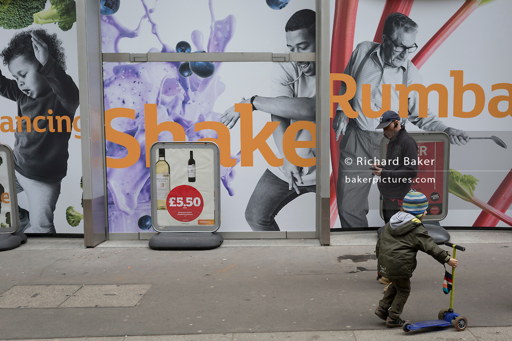 A young boy with a scooter passes a Sainsbury's poster, on 13th February 2017, in the City of London, United Kingdom.