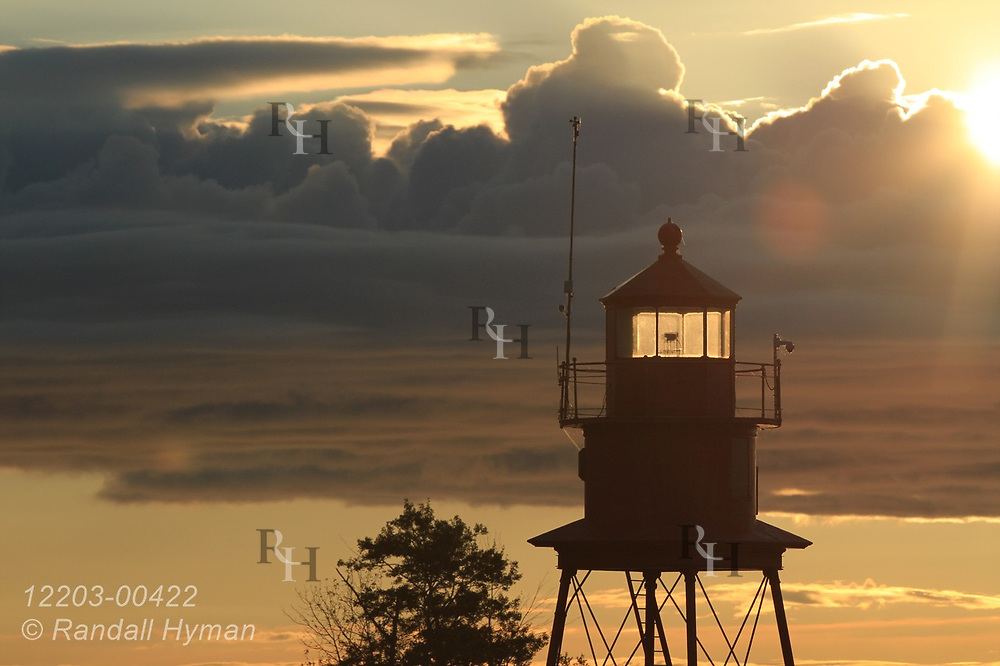 Lake Huron sunrise backlights small lighthouse beacon on a September morning in Alpena, Michigan.