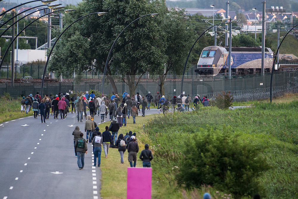 © London News Pictures. Calais, France. A large group of immigrants rush towards the train tracks at Eurotunnel at Calais.  Migrants attempting to reach the UK via the Eurotunnel at Calais in France. The situation has reached crisis point, which French police over run by attempts to cross the border. Photo credit: Ben Cawthra /LNP