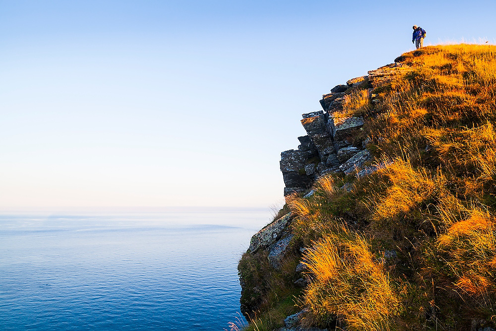 Parmenter Welty stands on a high bluff of Vaeroy Island, Lofoten Islands, Norway.
