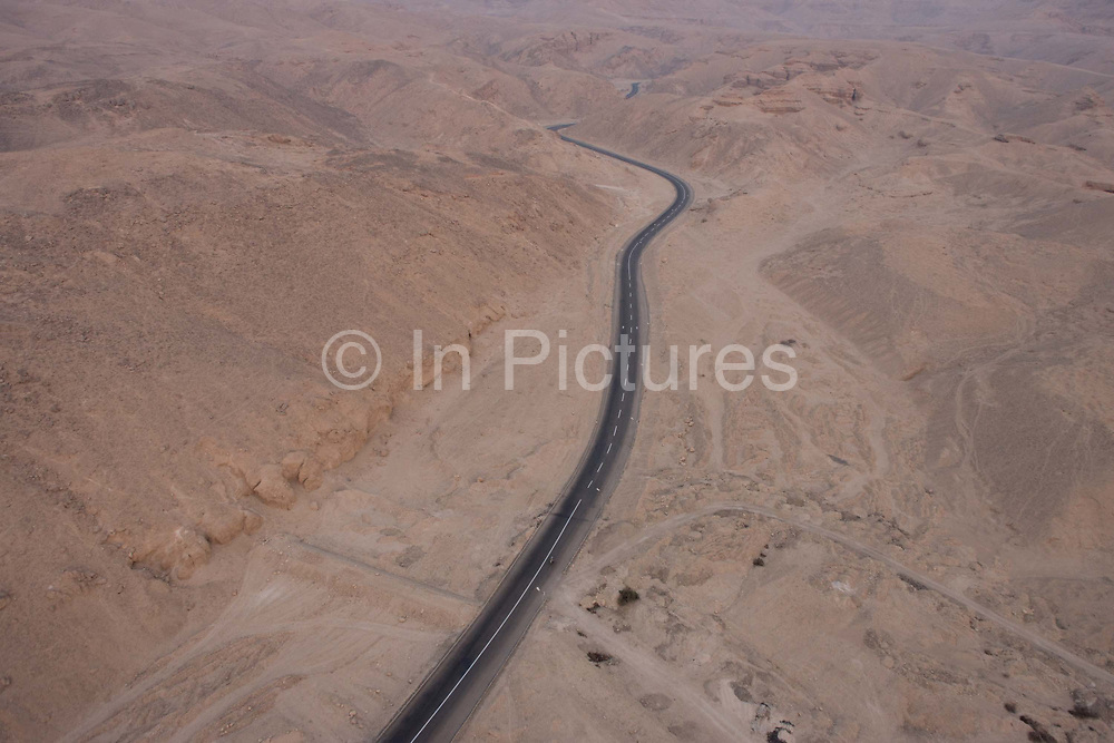 An aerial dawn landscape, looking down from a hot air balloon on to the road to the Valley of the Kings on the West Bank of the modern city of Luxor, Nile Valley, Egypt. The area has been a major area of modern Egyptological exploration for the last two centuries. The Valley was used for primary burials from approximately 1539 BC to 1075 BC, and contains at least 63 tombs. After that, the area was a site for tourism in antiquity (especially during Roman times).