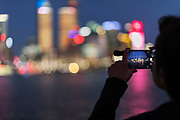 Over the shoulder view of a male tourist photographing the futuristic skyline of Lujiazui, Shanghai, China