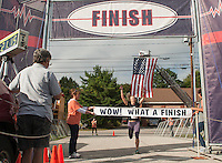 Ashley Linder of Laconia crosses the finish line during the 5K run on Saturday's 2013 WOW Fest festivities from the Laconia Athletic and Swim Club.    (Karen Bobotas/for the Laconia Daily Sun)
