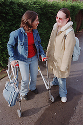 Teenage girl with physical disability using walking frame for support talking to college friend,