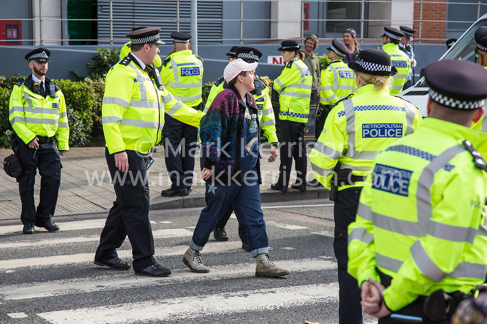London, UK. 7 September, 2019. Metropolitan Police officers usher an activist off a zebra crossing in front of a truck delivering to ExCel London on the sixth day of Stop The Arms Fair protests against DSEI, the world's largest arms fair. The sixth day of protests was billed as a Festival of Resistance and included performances, entertainment for children and workshops as well as activities intended to disrupt deliveries to ExCel London for the arms fair.