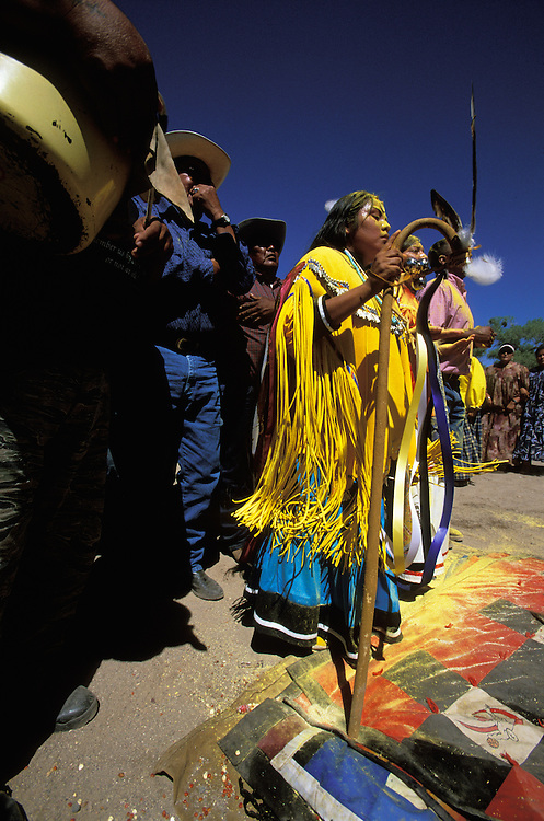 An Apache girl dances with her godmother and godfather at her Sunrise Dance, a first menstruation rite, on the San Carlos Apache Indian Reservation in Arizona, USA. The three are covered with sacred yellow pollen from the cattail plant, which has been applied as a blessing by the medicine man and the relatives. The Sunrise Dance is an enactment of the Apache creation myth and during the rites the girl 'becomes' Changing Woman, a mythical female figure, and comes into possession of her healing powers. The rites are also supposed to prepare the girl for adulthood and to give her a long and healthy life without material wants.
