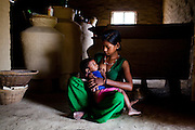 Pramila Tharu, 15, breastfeeds her 2 year old toddler Prapti, in Bhaishahi village, Bardia, Western Nepal, on 29th June 2012. Pramila eloped and married at 12 and gave birth to Prapti at age 13. She delivered prematurely on the way to the hospital in an ox cart and her baby weighed only 1.5kg at birth. In Bardia, StC works with the district health office to build the capacity of female community health workers who are on the frontline of health service provision like ante-natal and post-natal care, especially in rural areas. Photo by Suzanne Lee for Save The Children UK