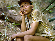 Portrait of a Yumbri ethnic minority man at the groups camp in the forests of the Nam Poui NPA (National Protected Area), Sayaboury province, Lao PDR. The Yumbri otherwise known as Yellow Leaves, Tong Luang or Mlabri are the last remaining hunter-gatherer Austroasiatic-speaking community living in the primary forests and river basins of the Nam Poui region in Sayaboury province. They migrate by group in the forest seeking edible natural resources. They are Laos' smallest ethnic group with estimates of the numbers of Yumbri remaining varying between 21 and 30 individuals.