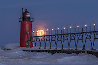 The full moon is captured in the catwalk of the South Haven lighthouse