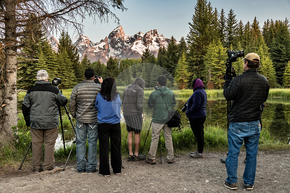 Photographers later to take photos of the Grand Teton mountains reflected at sunrise on the Snake River at Schwabacher Landing in the Grand Teton National Park near Moose, Wyoming.