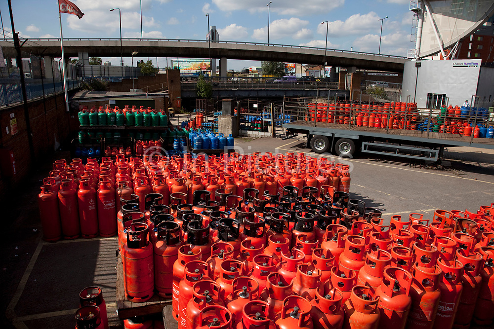 Red gas cannisters at a depot near Bow Interchange, East London. These cannisters are filled, used and refilled to be reused.
