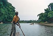 Rafting on the Rio Grande, Port Antonio, Jamaica, Caribbean 1970 man punting raft boat along river through tropical rainforest