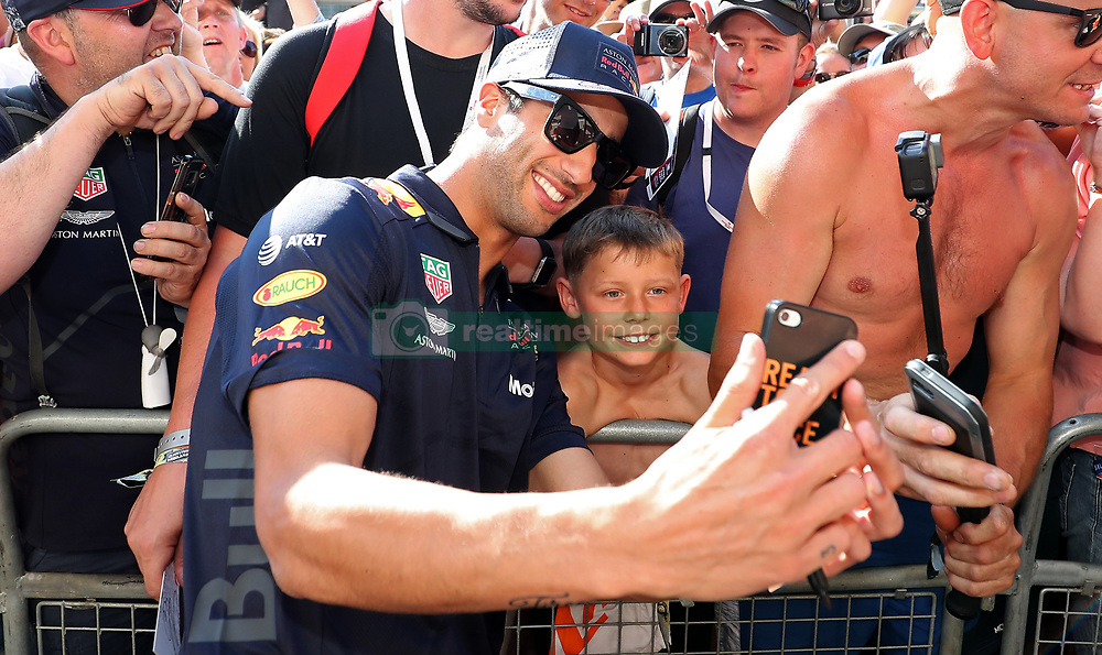 Red Bull's Daniel Ricciardo has a photo with a young fan during the paddock day of the 2018 British Grand Prix at Silverstone Circuit, Towcester.