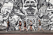 A group of people walk past graffiti on a wall in Hoxton, Shoreditch, London, UK<br /> Shoreditch, an area that was dominated by light industry is now home to creatives and the streets are often used as a backdrop for fashion shoots.