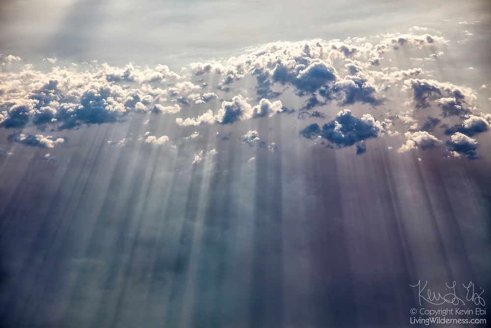 Cumulus clouds cast shadows on a layer of haze over the North Cascades in Washington state.
