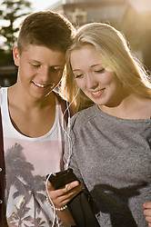 Teenage couple listening music with smart phone, smiling