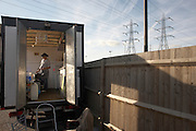Pregnant lady serving fast-food in a mobile burger bar trailer in an overnight lorry park on the A126 in industrial Grays