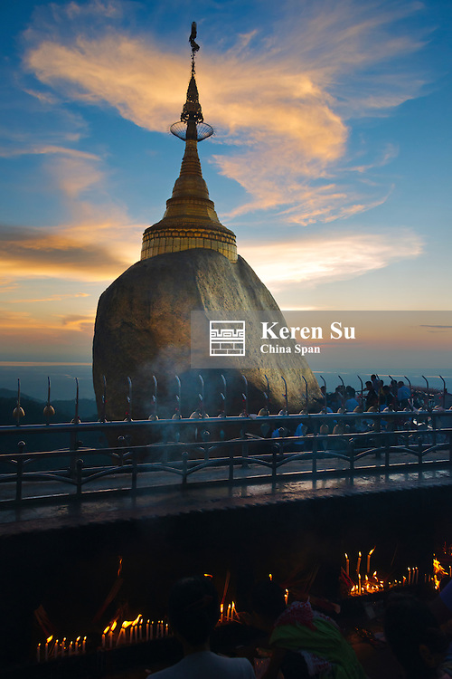 Pilgrims praying at Kyaiktiyo Pagoda (Gold Rock) at sunset, a small pagoda built on the top of a granite boulder covered with gold leaves pasted on by devotees, Mon State, Myanmar