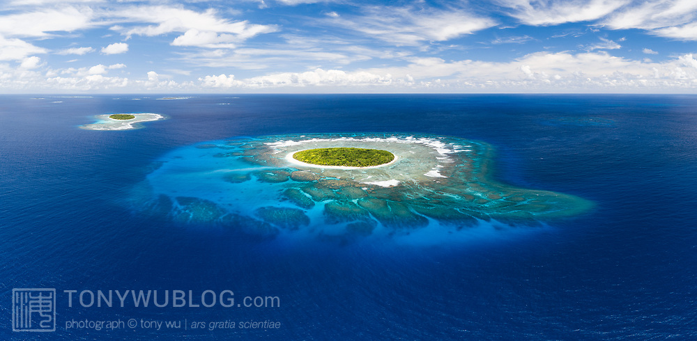 This is an aerial panorama of Fangasito Island in the Vava'u island group of the Kingdom of Tonga. Visible in the background is Fonua'one'one Island. The extensive coral reef structure surrounding the island is clearly visible from this high vantage point.