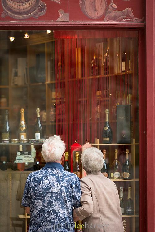 Senior couple looking through window of wine shop, Reims, France