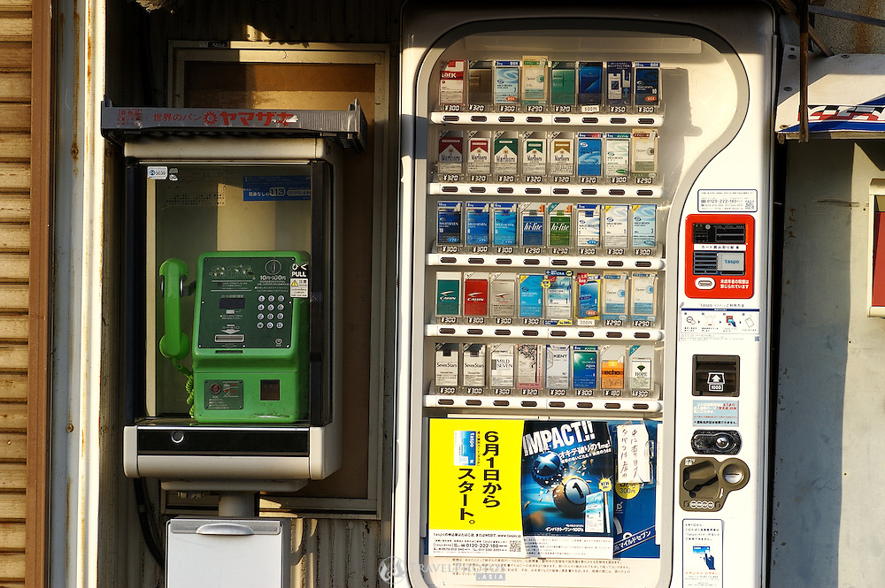 An old Japanese public phone and cigarette machine outside a dilapidated building