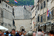 Street scene and section of wall, with tourists in foreground out of focus, and several Croatian flags flying. Dubrovnik old town, Croatia