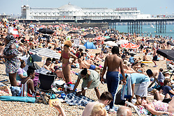 © Licensed to London News Pictures. 22/07/2021. Brighton, UK. Beachgoers enjoy the sun. As COVID restrictions relax and the UK continues to open up, Brighton experiences an influx of visitors making the most of the summer heat. Meanwhile transmission of the virus continues to double every 9 days. Photo credit: Guilhem Baker/LNP