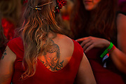 Glastonbury Festival, 2015<br /> Girl in red top with a buddha tattoo on her back.