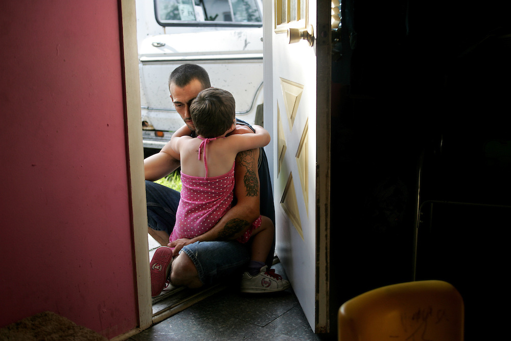 """Scott Elgin embraces his daughter Emilie, 3, in the doorway of their home in St. Petersburg, Florida.  Elgin was granted custody when Emilie's mother developed a drug addiction.  """"When I first got her, I didn't have any patience,"""" says Elgin.  """"It's something I've had to work on."""""""
