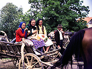 Women sitting on horse and cart carriage wearing traditional clothes, rural countryside area, Romania, eastern Europe 1967