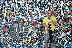 Musician busking on street beside Berlin Wall at the East Side Gallery in Berlin Germany