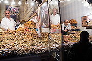 Vendors in their stalls piled high with Moroccan sweets wait for customers at a market in the Marrakech medina, Morocco on November 15, 2007.