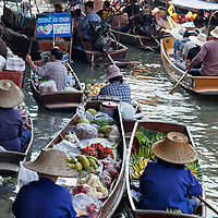 """According to """"Wikipedia"""" - Damnoen Saduak Floating Market consists of a maze of narrow khlongs (canals), and can be navigated by boat. Female traders, often wearing traditional mo hom apparel (blue farmers' shirts) with wide-brimmed straw hats (ngob) use sampans (small wooden boats) to sell their wares, often produce that comes directly from farms. These boats are often full of vegetables and colorful fruits that are photogenic, and these images are used for tourism promotion. The market is often the busiest in the morning around 7 am to 9 am, and is active until noon."""