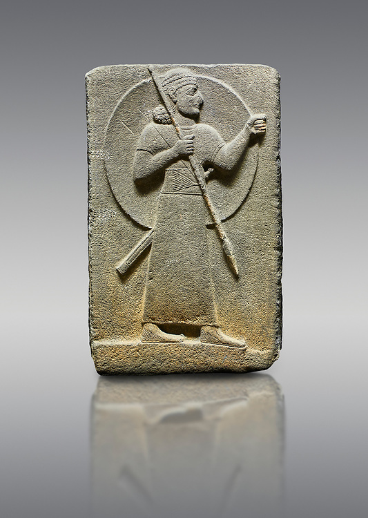Picture & image of Hittite relief sculpted orthostat stone panel of Royal Buttress. Basalt, Karkamıs, (Kargamıs), Carchemish (Karkemish), 900-700 B.C.  Warrior.  Anatolian Civilisations Museum, Ankara, Turkey.<br /> <br /> The figure with a long dress, a thick belt and curly hair has a large egis on his back. The figures carries a spear in his right hand and a long sword at his waist.  <br /> <br /> Against a gray background. .<br />  <br /> If you prefer to buy from our ALAMY STOCK LIBRARY page at https://www.alamy.com/portfolio/paul-williams-funkystock/hittite-art-antiquities.html  - Type  Karkamıs in LOWER SEARCH WITHIN GALLERY box. Refine search by adding background colour, place, museum etc.<br /> <br /> Visit our HITTITE PHOTO COLLECTIONS for more photos to download or buy as wall art prints https://funkystock.photoshelter.com/gallery-collection/The-Hittites-Art-Artefacts-Antiquities-Historic-Sites-Pictures-Images-of/C0000NUBSMhSc3Oo