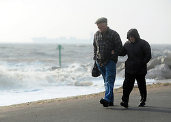 © Licensed to London News Pictures. 24/10/2011. Felixstowe, UK. A couple wrapped up against the weather, walk along the seafront. Windy weather along Felixstowe promenade today 24th October 2011. Parts of the UK are braced for wet and windy weather over the next 24hrs . Photo: Stephen Simpson/LNP