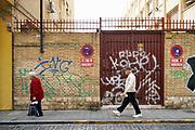 Spanje, Valencia, 4-11-2019Een oudere man en vrouw lopen langs een muur in de stad, binnenstad, stadscentrum, waarop veel graffiti is gespoten.Foto: Flip Franssen