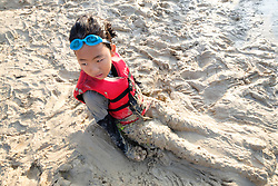"""Kid buried in sand at the """"Rockin' the River"""" July 4th celebration on the Trinity Trails at the Panther Island Pavilion, Trinity River, Fort Worth, Texas, USA."""