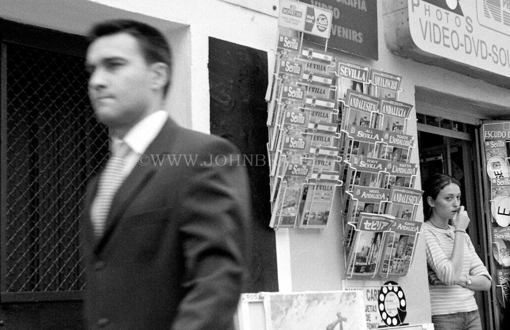 Black and white photo of a man in a suit walking by a girl and a souvenir stand in Sevilla, Spain.