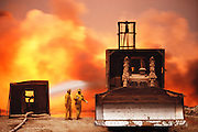 Oil well fire fighting specialists from the Texas company Boots and Coots shield themselves from the intense heat of the fire so that they can more closely direct other workers using equipment on the end of long booms attached to shielded bulldozers in the Kuwait oil fields. The company was one of those brought in to fight the Kuwait oil well fires after the end of the Gulf War. More than 700 wells were set ablaze by retreating Iraqi troops creating the largest man-made environmental disaster in history.