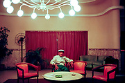Man in newsboy cap sitting in Miami hotel lobby