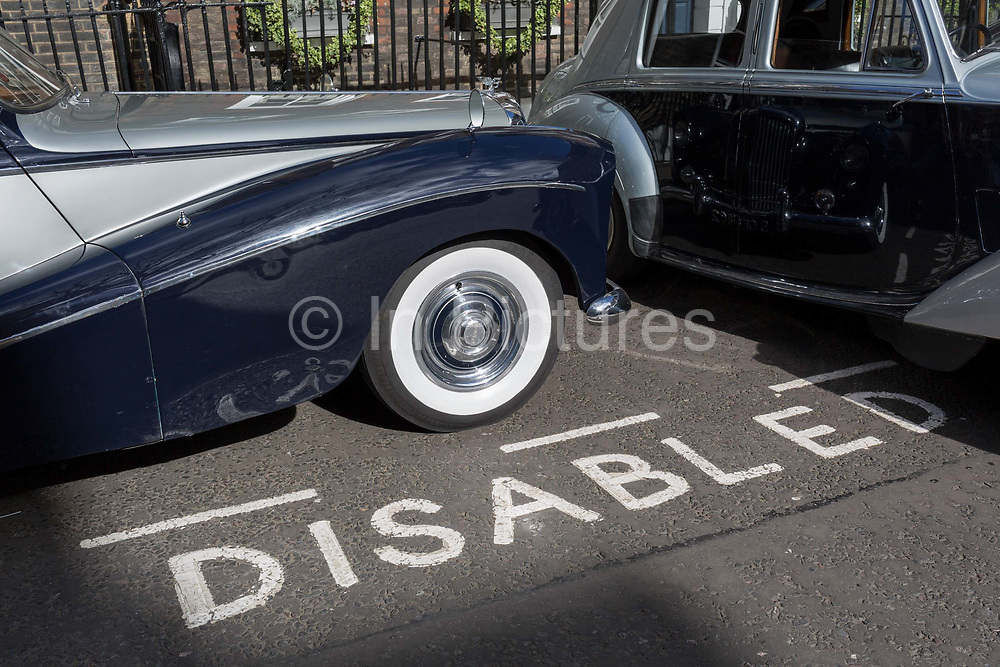 A 1964 Empress Bentley is parked in a Disabled bay in Smith Square, a small square behind the Houses of Parliament, before collecting its VIP passengers - barristers who are being sworn in as QCs aka Silks in legal vernacular, on 11th March 2019, in London, England.