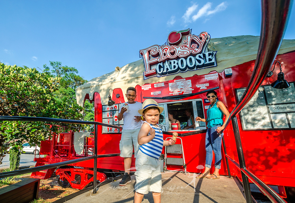 Robert Rojas (center), 3, gives a thumbs up after getting a chocolate ice cream cone with his brother, Gabriel Alvarez (left), 9, and his mother, Aurelina Alverez, right, May 20, 2014, at Frosty Caboose in Chamblee, Georgia. (Photo by Carmen K. Sisson/Cloudybright)