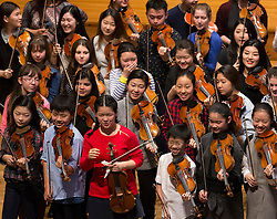 © Licensed to London News Pictures. 07/04/2016. London, UK.  One ot two of 43 of the world's best young violinists laugh as they gather for the Menuhin Competition at The Royal Academy of Music. To celebrate the 100th anniversary of Yehudi Menuhin's birthday, the Menuhin Competition returns to London for the first time since 2004. International soloists and 44 of the world's best young violinists will star in an 11-day festival of concerts and events from 7-17 April 2016. Photo credit: Peter Macdiarmid/LNP
