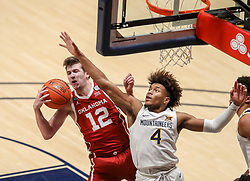 Feb 13, 2021; Morgantown, West Virginia, USA; Oklahoma Sooners guard Austin Reaves (12) grabs a rebound over West Virginia Mountaineers guard Miles McBride (4) during the second half at WVU Coliseum. Mandatory Credit: Ben Queen-USA TODAY Sports