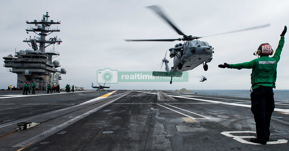 WATERS SOUTH OF JAPAN (Aug. 7, 2018) Aviation Ordnanceman Airman Myles Collins directs an MH-60S Sea Hawk assigned to Helicopter Sea Combat Squadron (HSC) 12 to land on the flight deck of the Navy's forward-deployed aircraft carrier, USS Ronald Reagan (CVN 76). Ronald Reagan, the flagship of Carrier Strike Group 5, provides a combat-ready force that protects and defends the collective maritime interests of its allies and partners in the Indo-Pacific region. (U.S. Navy photo by Mass Communication Specialist 2nd Class Kenneth Abbate)180807-N-OY799-0014