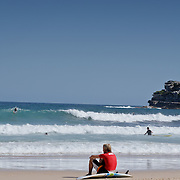 Surfer watching the sea seated on his board, waiting for the waves. Bondi Beach