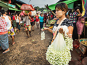 """25 OCTOBER 2015 - INSEIN, MYANMAR: A woman sells flower garlands at Danyin Market (also known as Da Nyin) in Insein, Myanmar, about 90 minutes from Yangon. Vendors in the market sell just about everything people in the area need, but mostly it's a """"wet market"""" with fruits, vegetables and meats. Most people in Myanmar still do not have refrigerators in their homes, so people go to market almost every day.    PHOTO BY JACK KURTZ"""