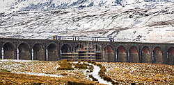 © Licensed to London News Pictures. 04/01/2021.Gearstones UK. A commuter train crosses Ribblehead viaduct this morning in the shadow of the snow covered Ingleborough mountain as work continues on a £2.1M restoration project to re-point eroded joints & replace stones on all 24 arches of the famous rail crossing.  Photo credit: Andrew McCaren/LNP